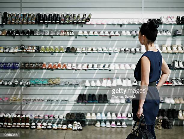 woman shopping looking at shelves of shoes - shoe store stock pictures, royalty-free photos & images
