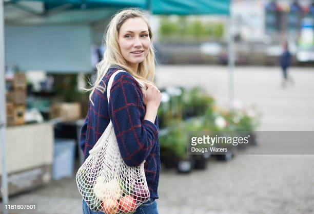 woman shopping on local market with plastic free bag. - local produce stock pictures, royalty-free photos & images
