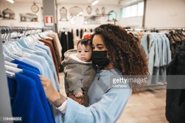 het winkelen van de vrouw op de dag van de verkoop met haar baby - autumn winter fashion collection stockfoto's en -beelden