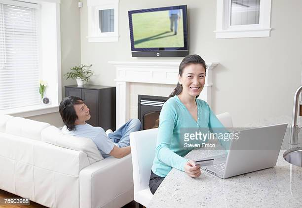 Woman shopping online and man watching television