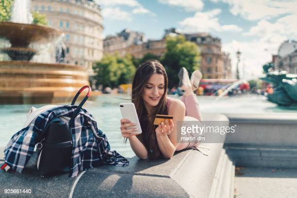 woman shopping online from smartphone - commercial activity stock photos and pictures