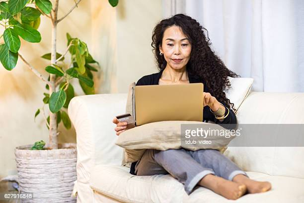 Woman shopping online with a digital tablet and credit card