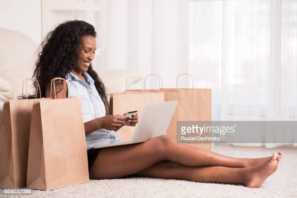 Woman shopping online with bags beside.
