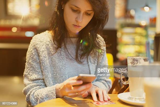 Woman shopping online with credit card in a cafe