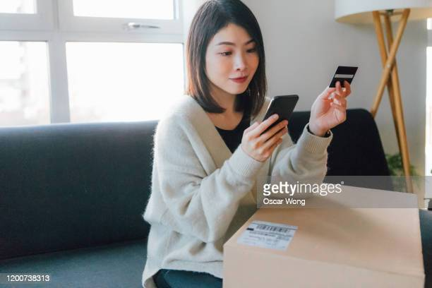 woman shopping online with mobile phone and credit card at home - asian stock pictures, royalty-free photos & images