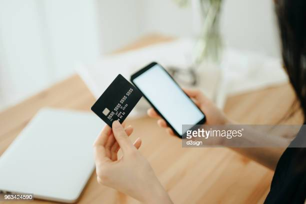 Woman shopping online with smartphone and credit card on hand