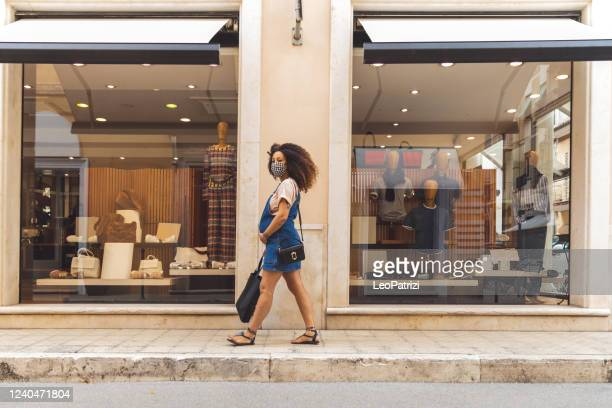 woman shopping protecting herself wearing protective mask - high street stock pictures, royalty-free photos & images