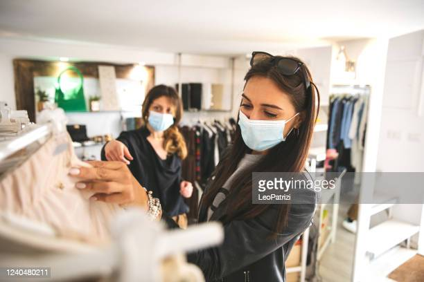 woman shopping protecting herself wearing protective mask - merchandise stock pictures, royalty-free photos & images