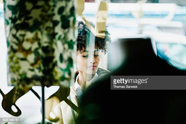 Woman shopping though window of boutique shop