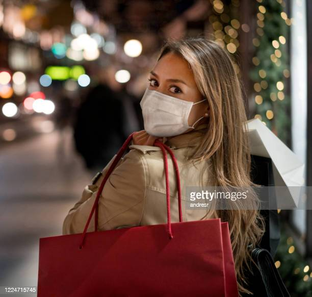 woman shopping wearing a facemask – covid-19 concepts - merchandise stock pictures, royalty-free photos & images