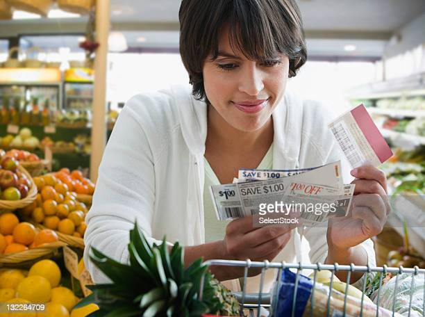 woman shopping with coupons - coupon stock photos and pictures