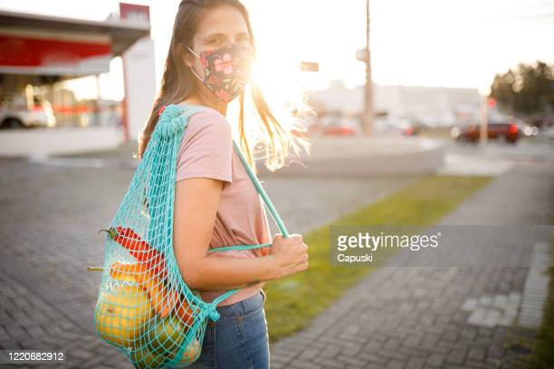 woman shopping with reusable bag wearing protective mask - cloth mask stock pictures, royalty-free photos & images