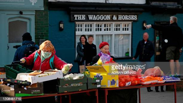 A woman shops at a fruit and vegetable market while people observe social distancing as they wait their turn in Hartley Wintney Hampshire on March 28...