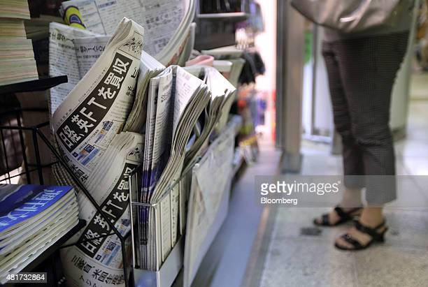 A woman shops at a kiosk as newspapers including the Nikkei left are displayed for sale in Tokyo Japan on Friday July 24 2015 After almost six...