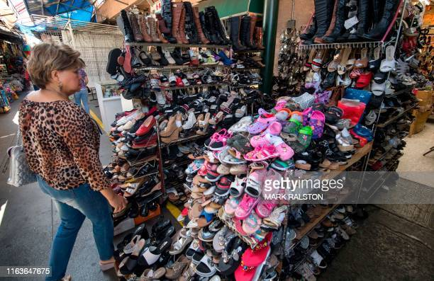 A woman shops for Chinese made shoes at a store in the Chinatown area of Los Angeles California on August 24 2019 President Donald Trump hit back at...