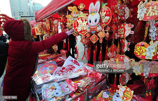 A woman shops for ornaments on January 21 2011 in Beijing for the Chinese New Year ahead of the Year of the Rabbit which begins on February 3rd The...