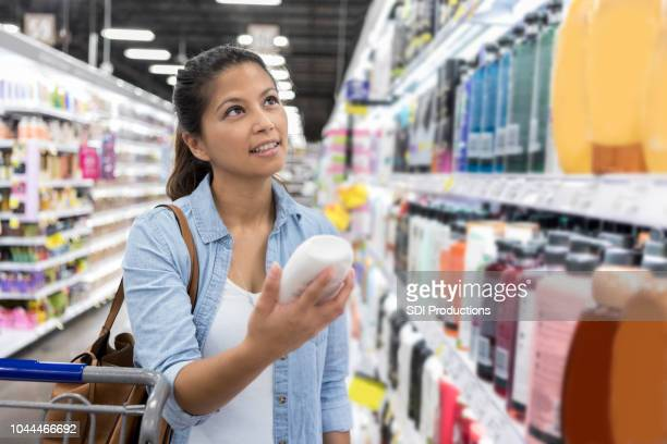Woman shops for shampoo in supermarket