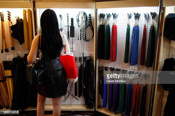A woman shops for whips in the exhibit hall of the domination convention DomConLA in the evening hours of May 10 2013 in Los Angeles California The...