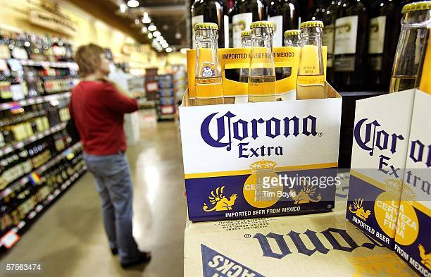 A woman shops for wine in the wine aisle near a sixpack of Corona Extra beer in a grocery store May 9 2006 in Des Plaines Illinois With new flavors...