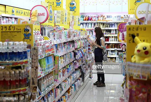 A woman shops in a drug store at a shopping mall in Tokyo Japan on Thursday Aug 8 2013 Japan's consumer prices are exceeding estimates by the most...