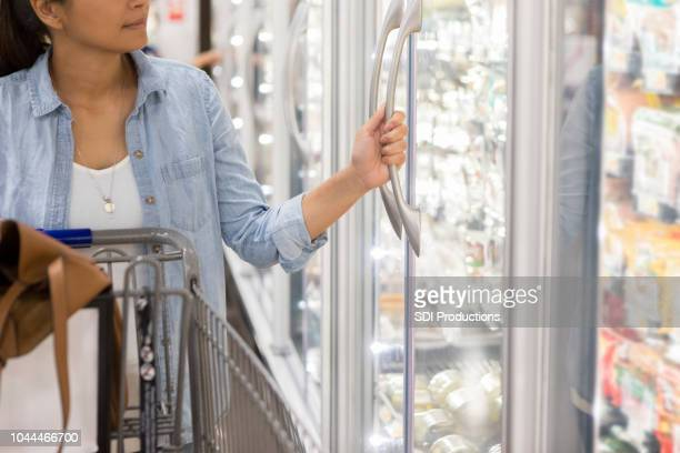 woman shops in refrigerated section in supermarket - freezer stock photos and pictures