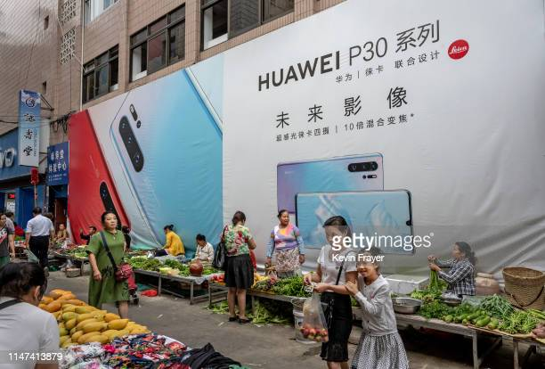 A woman shops with her daughter in front of a billboard advertising smartphones for China's Huawei Technologies Co at a market on June 1 2019 in...
