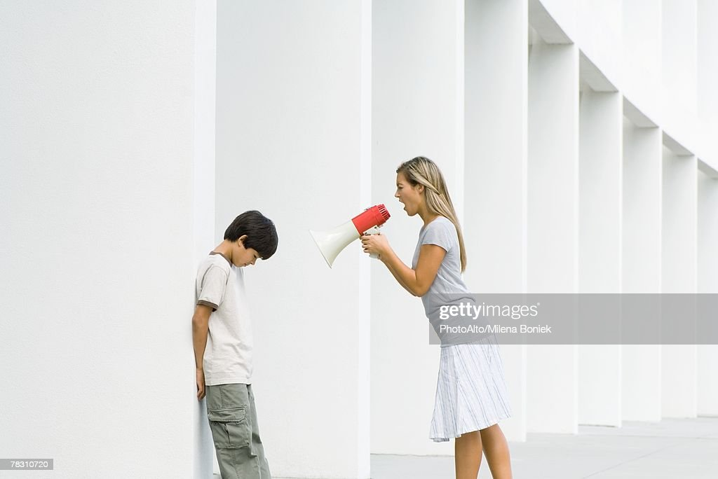 Woman shouting at boy through megaphone, boy lowering head : Stock Photo