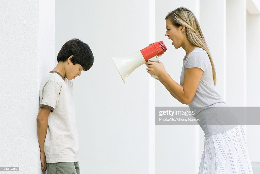 Woman shouting at boy through megaphone : Stock Photo