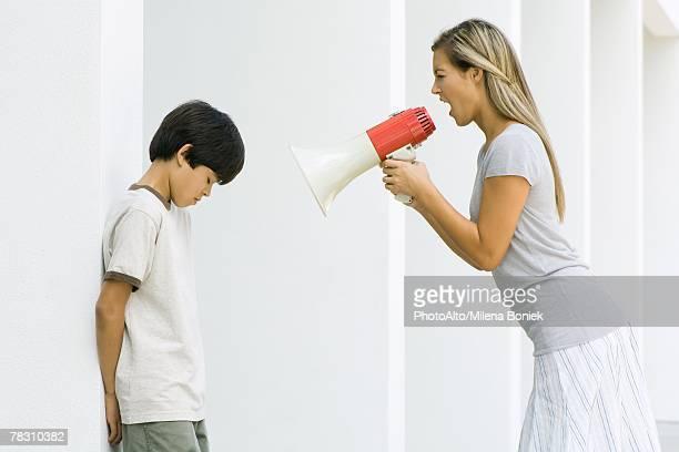 Woman shouting at boy through megaphone