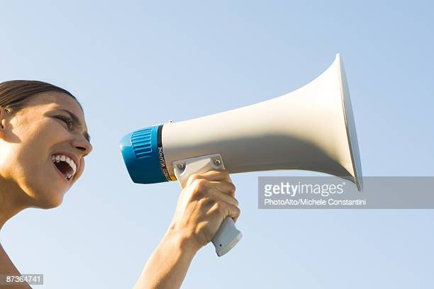 woman shouting into megaphone, low angle view, cropped - 自己主張 ストックフォトと画像