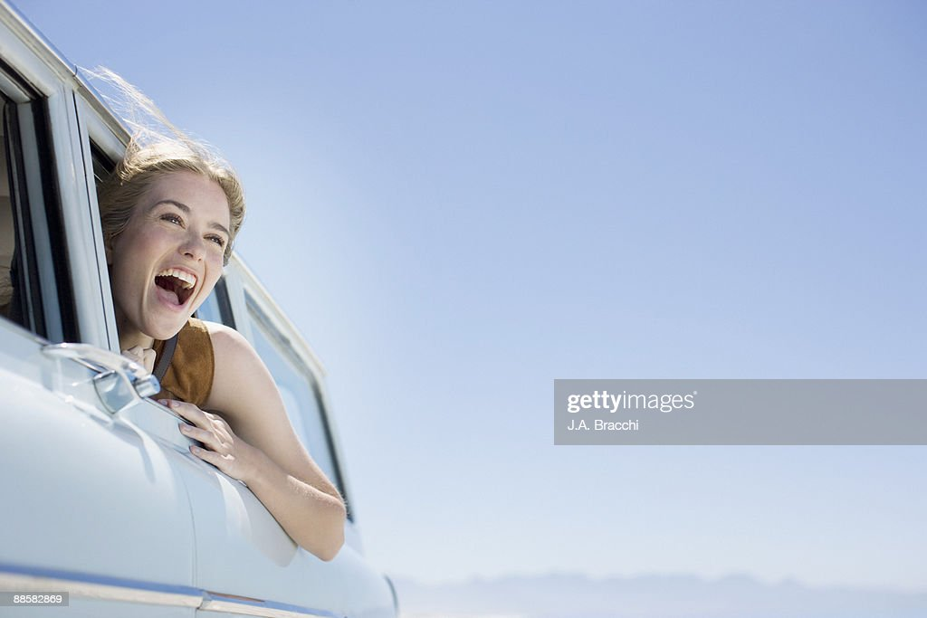 Woman shouting out car window : Stock Photo