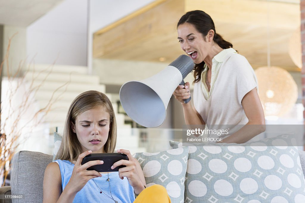 Woman shouting through a megaphone at his daughter for playing video game : Stock Photo