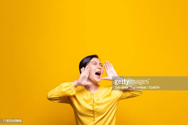 woman shouting while standing against yellow background - gridare foto e immagini stock