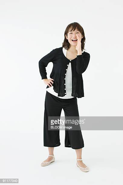 Woman shouting with hand on hip, portrait, studio shot