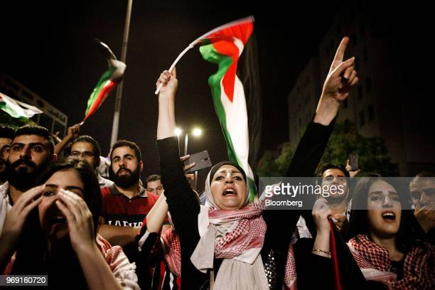 A woman shouts a slogan while waving a Jordanian national flag during a demonstration against a draft income tax law near the prime minister's office...