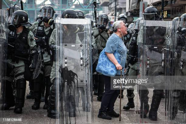 Woman shouts at police officers as they advance towards protesters in the district of Yuen Long on July 27, 2019 in Hong Kong, China. Pro-democracy...