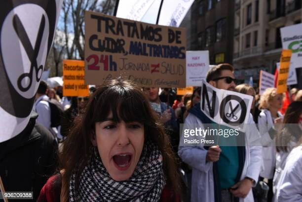 A woman shouts slogans as she takes part in a protest by Spanish doctor's unions against cuts in the Public Health system in Madrid