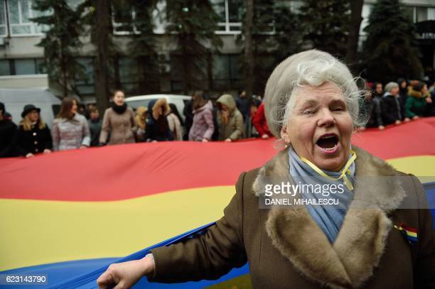 TOPSHOT A woman shouts slogans next to people carrying a giant Moldovan flag during a protest in downtown Chisinau against what they consider to be a...