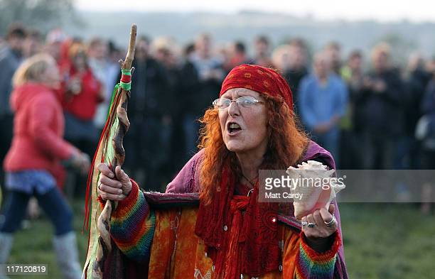 A woman shouts to festival goers as they gather at the Stone Circle to see the sun set at the Glastonbury Festival site at Worthy Farm Pilton on June...