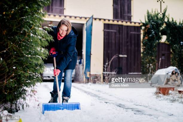 woman shoveling snow in yard. - snow shovel stock photos and pictures