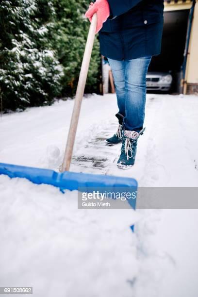 Woman shoveling snow.