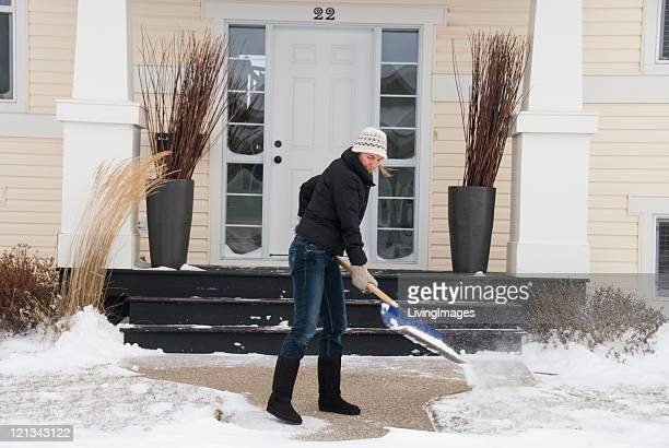 Woman shoveling snow with a blue shovel on her back porch