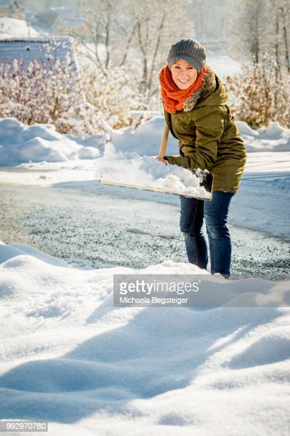 woman shovelling snow - snow shovel stock photos and pictures