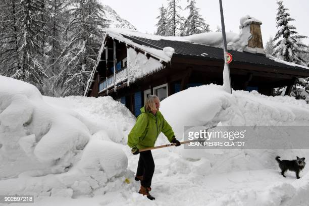 A woman shovels snow in the village of Val d'Isere as the precautions put into place for motorists due to an avalanche alert are lifted in the French...
