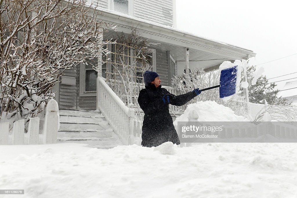A woman shovels snow on Shirley Street February 9, 2013 in Winthrop, Massachusetts. An overnight blizzard dropped two to three feet of snow, with coastal flooding expected as the storm lingers into the day.