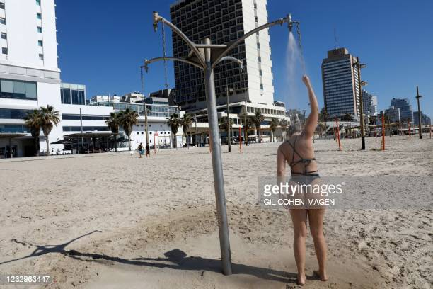 Woman showers on the beach in the Mediterranean city of Tel Aviv on May 18 as the UN Security Council was to hold an emergency meeting amid a...