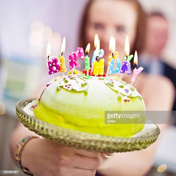 誕生日ケーキを示す女性