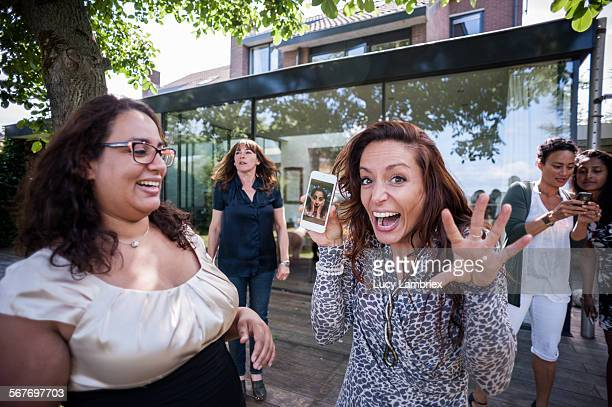 woman showing a funny photo on smartphone - offbeat stock pictures, royalty-free photos & images