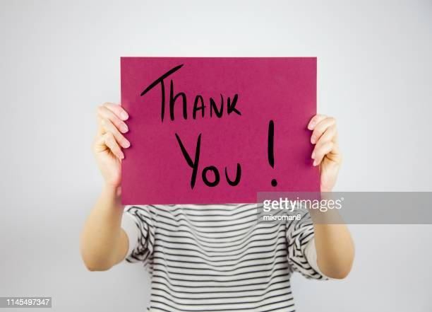 woman showing a paper page saying thank you - gratitude stock pictures, royalty-free photos & images