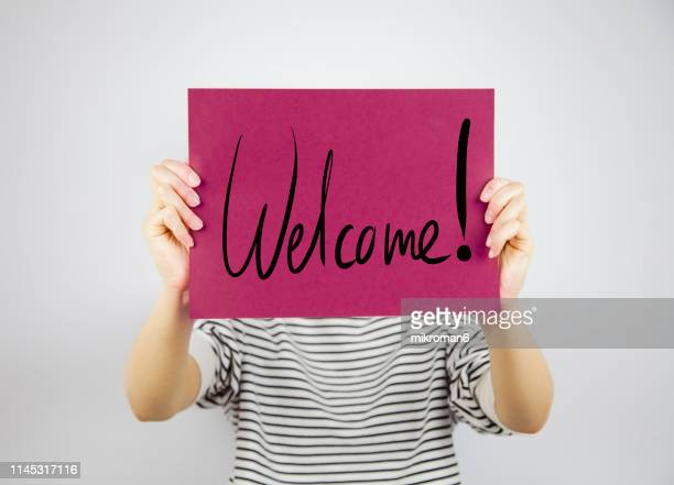 woman showing a paper page saying welcome - greeting stock-fotos und bilder